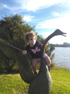 Little girl in a mask climbing on a statue of a swan.
